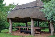 Mohutný stůl z jilmového kmene ukrývá před deštěm typický altánek s doškovou střechou.