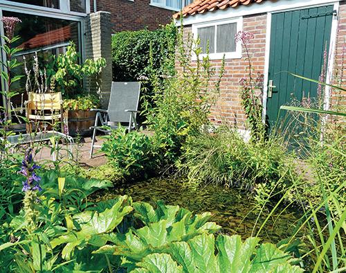 Propojení domu a zahrady zprostředkovává prostorná terasa s příjemným posezením u jezírka.