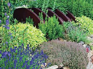 Kamennému ostrůvku s kvetoucími bylinkami a trvalkami dodávají plasticitu traviny.
