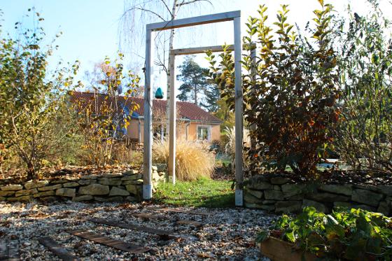 Okrasnou a  užitkovou část oddělují nejen kamenné zídky, ale i brána z dřevěných trámů.