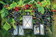 Kovové lucerny na stůl a prostý proutěný věneček mohou být základem letního venkovního lustru.