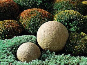 Kamenné koule přitáhnou pozornost zvlášť ve větším množství. Zde jejich efekt ještě zesilují zastřižené zimostrázy.
