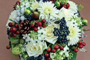 Svatební kytice v lesním stylu je vytvořená z růží, jiřin, plodů třezalky a kaliny, vřesu a borovicové šišky.