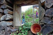 Vtipný průhled do sousední zahrady ve stěně z naskládaného dřeva.