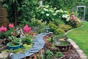 Během července 2014 vegetace učinila další pokrok – v popředí nad zídkou kvetou růžové čechravy (Astilbe 'Boogie Woogie'), v pozadí dřevité třezalky i první květy hortenzií.