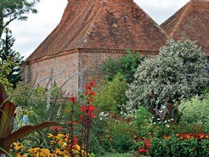 Kulisu zahradě vytvářejí budovy s výraznými bílými věžičkami na vrcholech střech. Jsou to staré sušárny chmelu, který se v této oblasti kdysi hojně pěstoval.