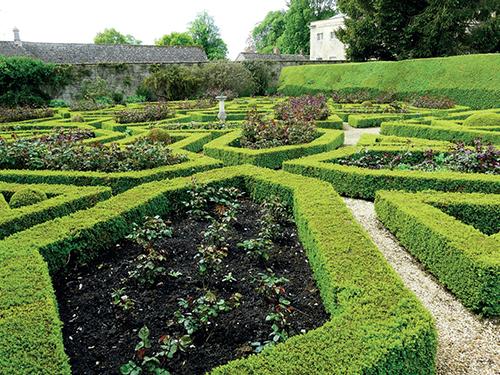 Poblíž holubího domu se rozkládá ornamentální zahrada s pečlivě udržovanými živými ploty.