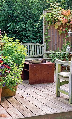 Dřevěnou terasu elegantně doplňují bohatě osázené velké květináče a pocit soukromí jí zajišťuje zástěna porostlá pnoucími rostlinami.