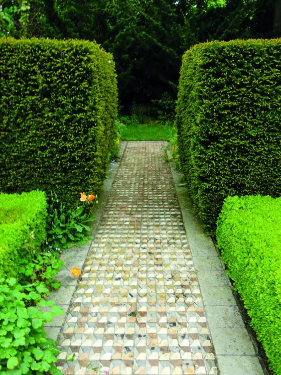 Pestrá dlažba může zahradu obohatit, jako je tomu vtomto případě. Ačkoliv se zpevněná plocha skládá hned zněkolika materiálů všedé a zemité barvě, rozhodně prostor netříští, ba právě naopak skvěle vyniká vedle barevně sjednocené vegetace. Hůře by ovšem působila ve chvíli, kdy by byla obklopena pestrým trvalkovým záhonem, který by stakovouto dlažbou soupeřil o pozornost.